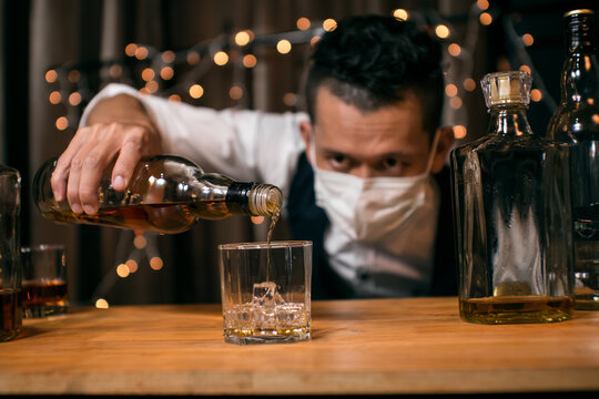 Barman pouring whiskey wearing  protective mask on the bar counter