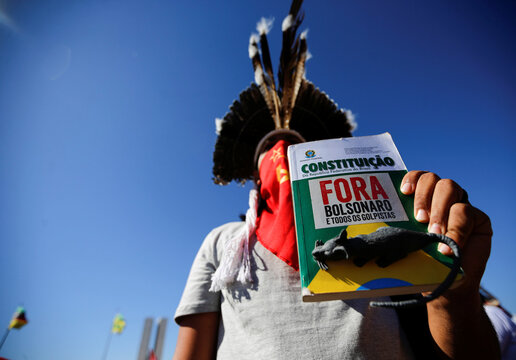 """A demonstrator holds a book of the Brazilian constitution, with a sign that reads """"Out Bolsonaro"""" during a protest against Brazil's President Jair Bolsonaro in front of the National Congress, in Brasilia"""