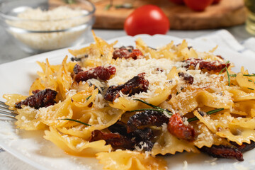 Pasta with sun dried tomatoes and parmesan in a white plate on the table. Italian food dish, close up