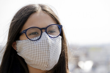 Close up of teenage girl wearing homemade face mask outdoors