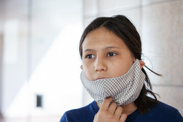 Close up of teenage girl wearing homemade face mask indoors