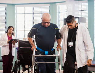 Senior man exercising with therapists during physical therapy