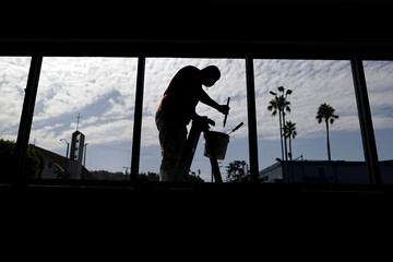 A worker paints window frames during summer break renovations and installation of social distancing measures at St. Joseph's School, amid the outbreak of the coronavirus disease (COVID-19), in La Puente