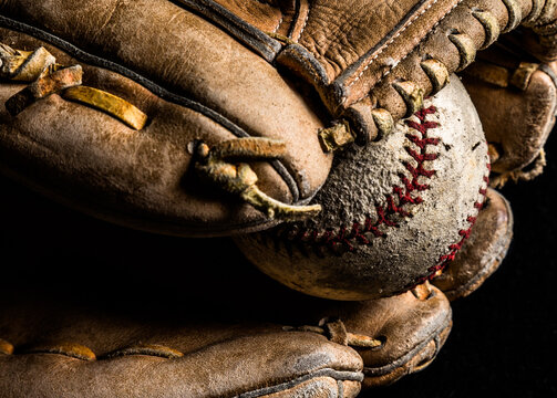 Closeup of old baseball in worn out leather glove