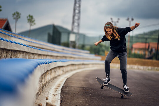 Teenage girl performing skateboard tricks on the sports field.