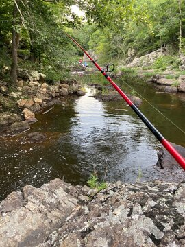 Fishing pole overlooking a mountain stream with fishermen in the far distance