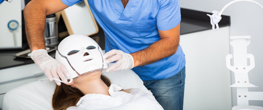 Skilled male beautician applying light therapy LED facial mask to woman at esthetic clinic. Trendy skin rejuvenation treatment to face