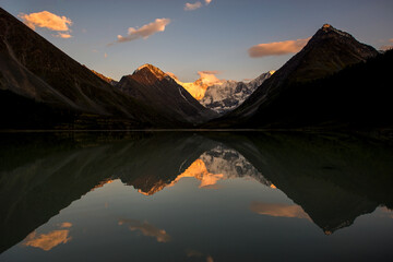 Belukha peak at sunset is reflected in the mountain lake AK-Kem