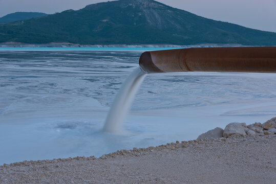 Industrial wastewater is discharged from pipe into the water