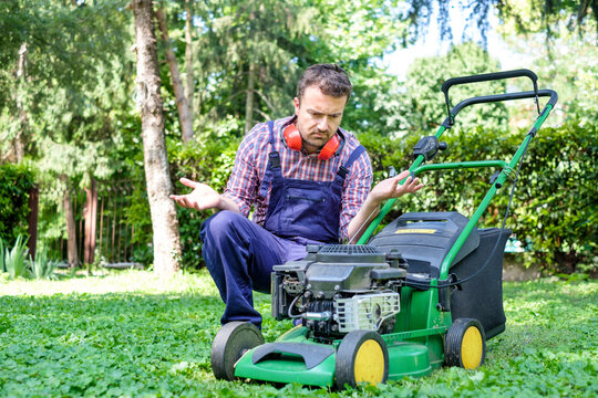 One guy portrait cutting the garden grass having problem with the lawn mower