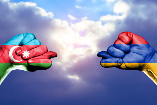 Trade and military conflict between Azerbaijan and Armenia. Conceptual photo of two fists with figs isolated on a white background.