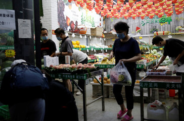 People wearing face masks, following the outbreak of the coronavirus disease (COVID-19), buy fruits and vegetables at a store in Beijing