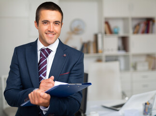 Portrait of positive business man with folder of documents at office