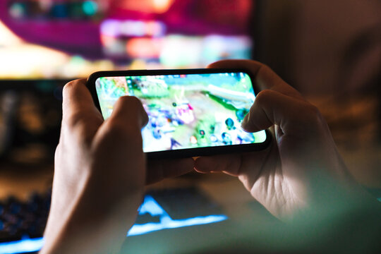 Image closeup of focused man playing video game on mobile phone