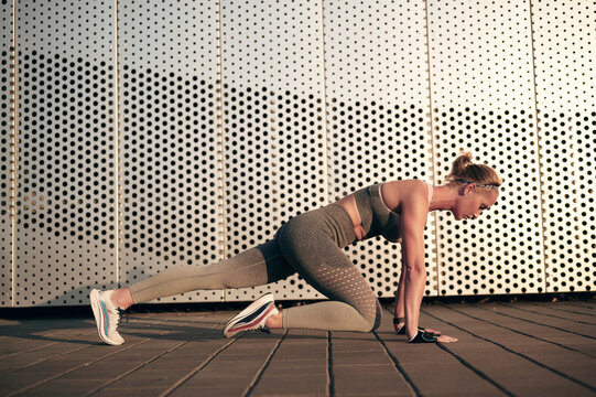 Strong fitness woman is doing mountain climber exercises in front of wall outdoor