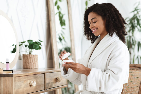 Daily Beauty Routine. Black Woman Opening Jar With Moisturising Cream At Home