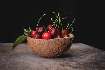 Coconut shell bowl full of fresh cherries in the shell on a wooden table on black background