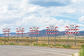 Five road closed signs mark the end of this New Mexico highway.