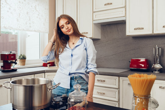 Pensive young woman standing in the kitchen and thinking of what to cook