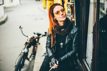 Red hair woman in black rock style leather jacket e at the autumn city.