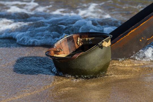 Wet Amcerian WW2 M1 helmet left behind on the  beach.  D-Day reenactment event day. Hel, Poland