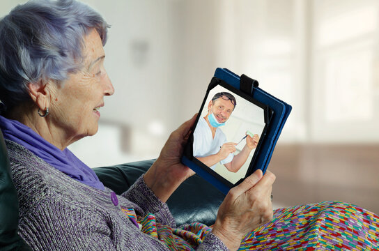 Telemedicine engages an elderly female patient to connect with her dentist in a convenient way. Doc explains her particular dental needs on the screen of the senior woman's tablet.