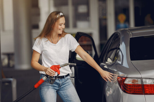 Woman on a gas station. Lady in a white t-shirt. Woman near the car.