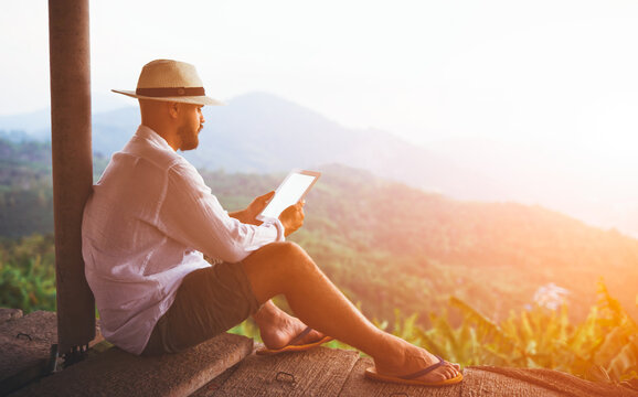 Young man traveler is holding digital tablet with empty screen background with copy space for your advertising content. Male tourist is using touch pad, while is sitting against amazing jungle scenery