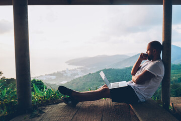 Tuinposter Wit Thoughtful young man looking away on beautiful nature landscape while sitting with laptop computer outdoors. Blogger guy catch inspiration writing article on netbook during vacation holidays in Thai