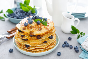Blueberry pancakes with butter, maple syrup and fresh berries. American breakfast