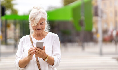 Portrait of senior woman using smartphone in the city