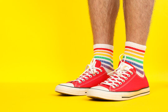 Male legs in red sneakers and LGBT socks on yellow background