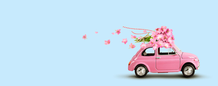 Pink car with bouquet of flowers on a roof on blue background. Copy space.