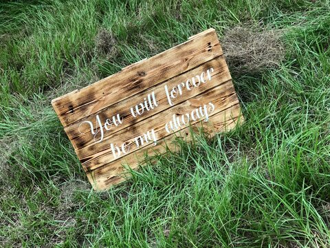 Romantic wooden sign on grass