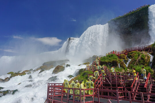 Niagara Falls, NY: Tourists in yellow raincoats enjoy the Cave of the Winds, stairs and platforms at the foot of the American Falls, on Goat Island.
