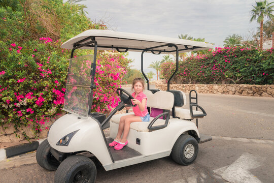 A child is playing a driver sitting on an electric car. Little girl is sitting behind the wheel of a golf cart. Little tourist has fun at a tropical resort