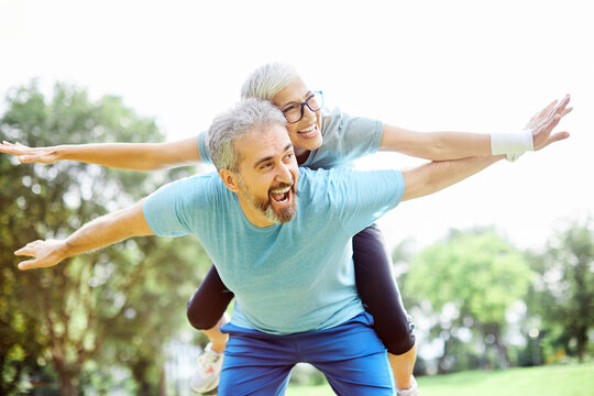 outdoor senior fitness woman man lifestyle active sport exercise healthy fit retirement love fun piggyback