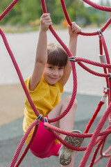 cute girl climbing the net in the playground