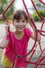 Photo sur Toile Doux monstres cute girl in pink t-shirt in the playground