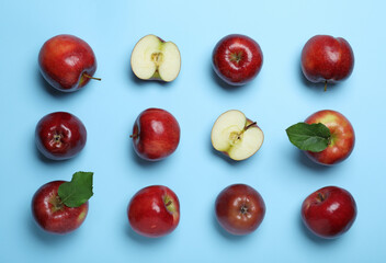 Tasty red apples on light blue background, flat lay