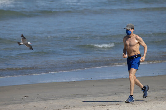 A man wearing a face mask runs along the beach as California reported its largest number of new coronavirus infections in a single day, during the outbreak of the coronavirus disease (COVID-19) in Del Mar
