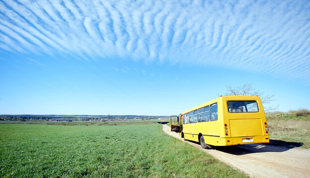 yellow old broken bus stands on a sandy road in a green field under the wind clouds