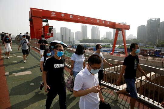 People wearing face masks walk on a foot bridge next to a construction site in Beijing