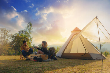 Papiers peints Camping Young couples have good time morning on camping trip with sunrise background. Couples enjoy camping with morning coffee.