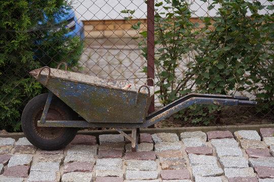 empty wheelbarrow in the yard of granite cube