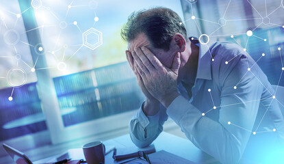 Stressed businessman sitting in office; light effect