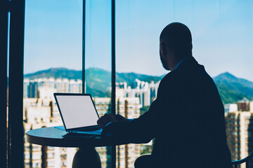 Businessman dressed in black elegant suit looking out of window while working on new startup...