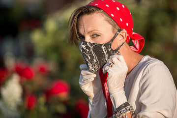 Woman in trendy fashion outfit during quarantine of coronavirus outbreak. Quarantine city lifestyle, young woman wearing protective mask and gloves on hands
