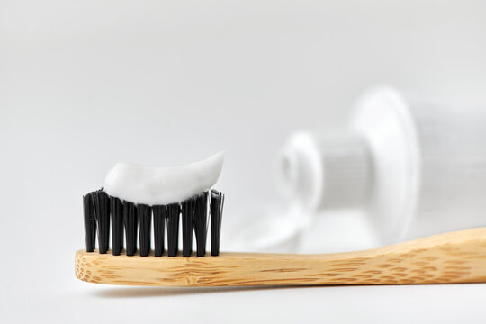 dental care, sustainability and eco living concept - close up of wooden toothbrush with white toothpaste on it