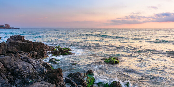 coast of the ocean at sunset. beautiful landscape with rocks in the water. gorgeous cloudscape above the sun and horizon. concept of calmness and mediatation